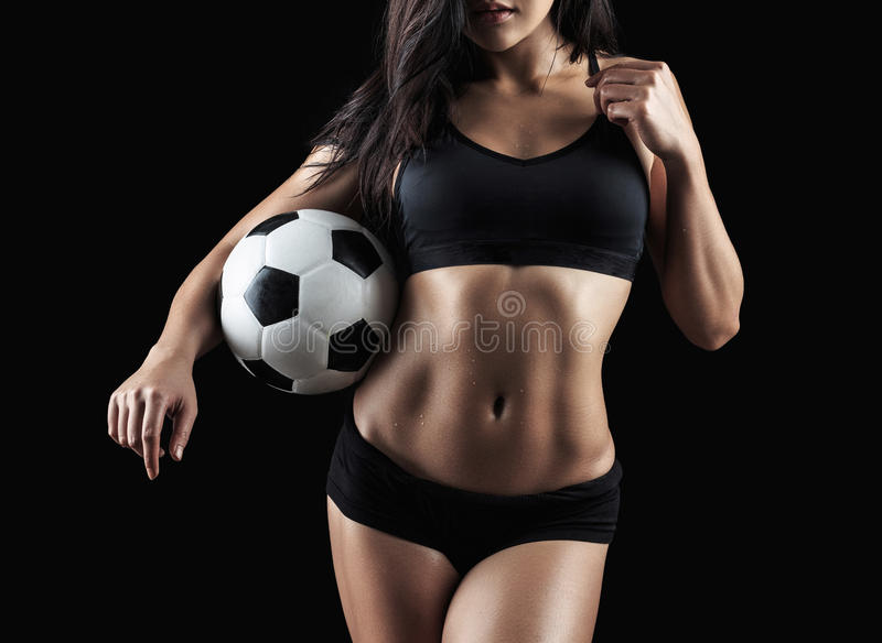 Beautiful body of fitness model holding soccer ball. Isolated on black background stock image