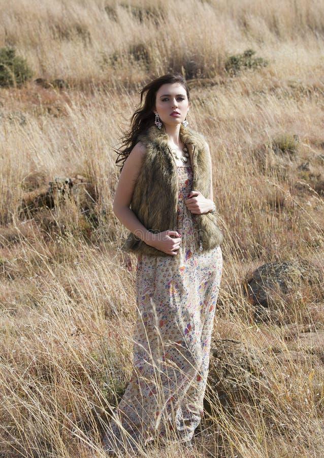 Beautiful bohemian brunette woman standing in a field of grass stock image