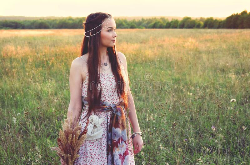 Beautiful boho girl standing in the field royalty free stock image