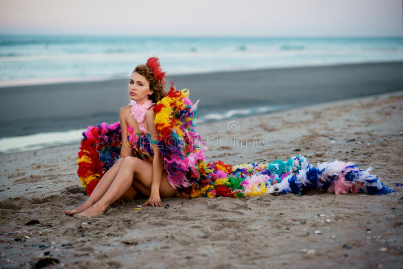 Beautiful boho styled girl with long hair on the sunset beach stock image