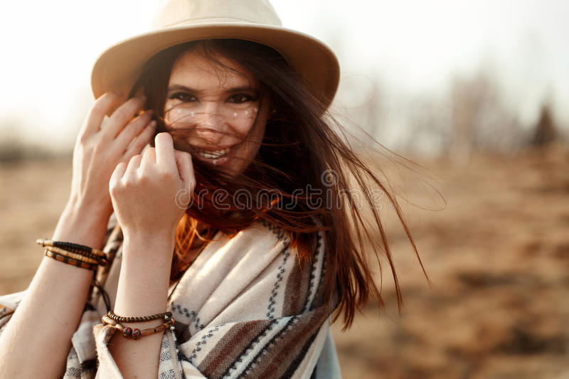 Beautiful boho woman hipster, smiling, wearing hat and poncho at sunset in mountains, true emotions, space for text. Beautiful boho woman hipster, smiling stock images