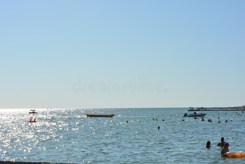 Beautiful border between the blue sky and the black sea with small waves and fine golden and bright reflections of the sun on the stock images