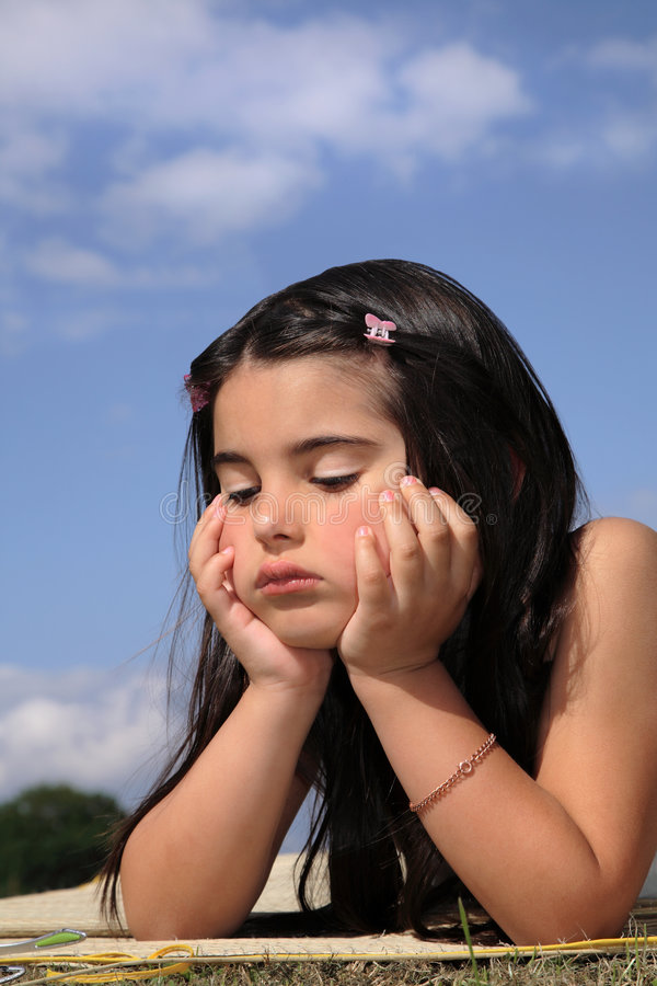 Beautiful Bored Little Girl. Beautiful young little girl resting her hands on her chin looking bored. Blue sky and clouds to the rear stock image