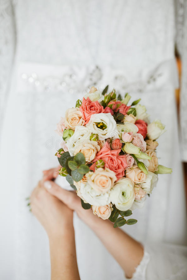 Beautiful bouqet in the hands of bride. The bride is standing beside the wedding dress and holding the bouqet royalty free stock photography