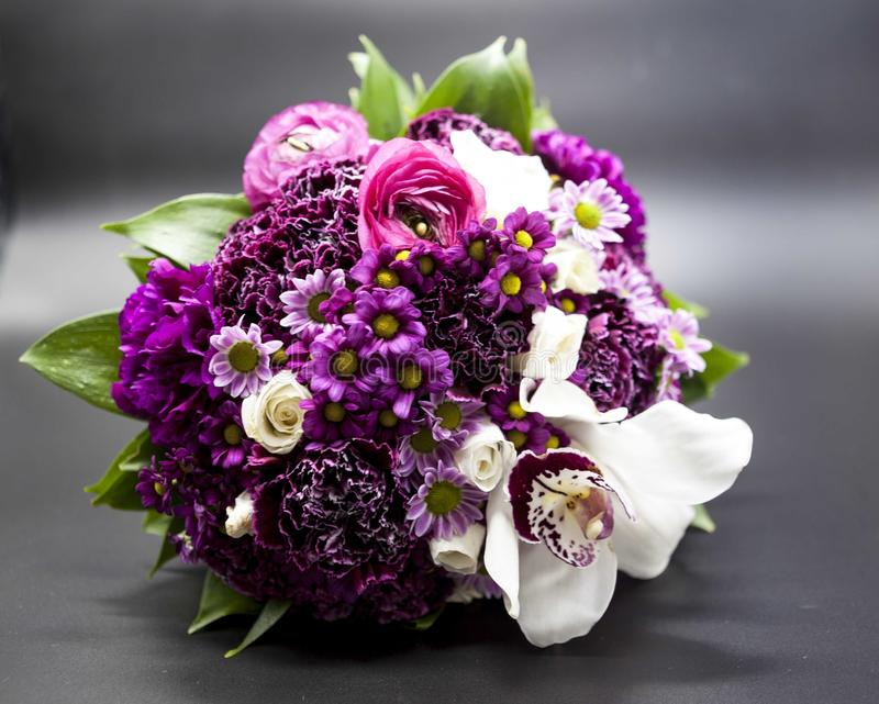 Beautiful bouquet of bride purple flowers on a dark background. stock photos