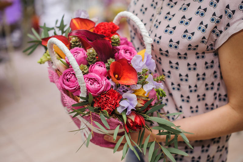 Beautiful bouquet of bright flower basket in hands stock image