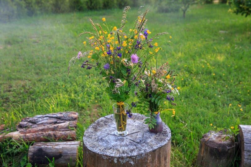 Beautiful bouquet of bright wildflowers on a background of green grass. Handmade beautiful bouquet of bright wildflowers on a background of green grass. Latvia stock photo