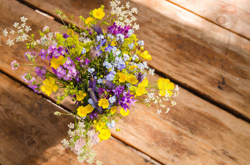 Beautiful bouquet of bright wildflowers on a wooden table background stock image