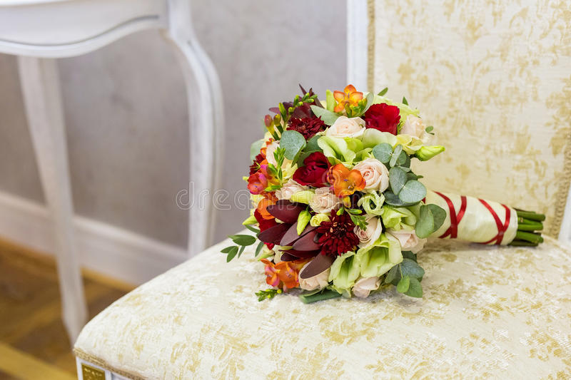 Beautiful bouquet of colorful flowers and green roses lying on a chair close-up stock photos