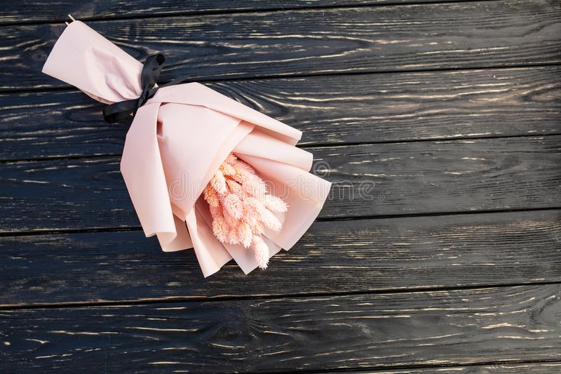 Beautiful bouquet of dry pink flowers on a wooden black background. Minimalism, space for text. Gift Card royalty free stock image