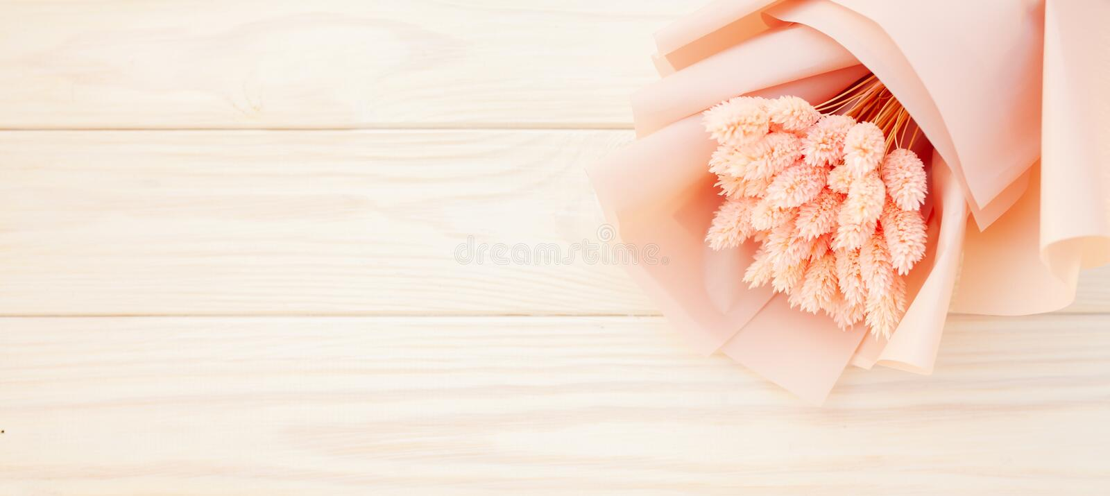 Beautiful bouquet of dry pink flowers on a wooden white background. Minimalism, space for text. Gift Card stock photo