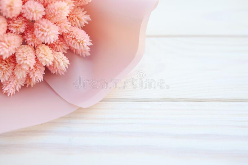 Beautiful bouquet of dry pink flowers on a wooden white background. Minimalism, space for text. Gift Card royalty free stock photography