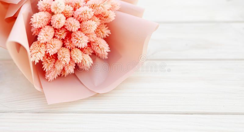 Beautiful bouquet of dry pink flowers on a wooden white background. Minimalism, space for text. Gift Card royalty free stock image