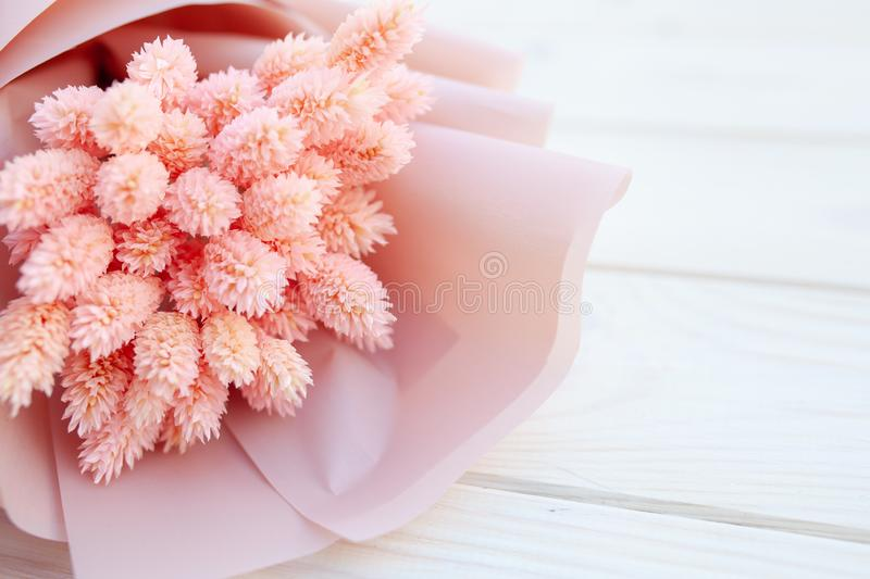 Beautiful bouquet of dry pink flowers on a wooden white background. Minimalism, space for text. Gift Card stock images