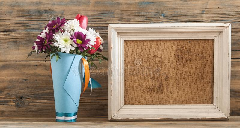 Beautiful bouquet of flower with photo frame on vintage wood background. royalty free stock photos