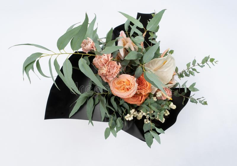 Beautiful bouquet of flowers in black mate paper. Roses and pink carnation View from above. White background. stock photography