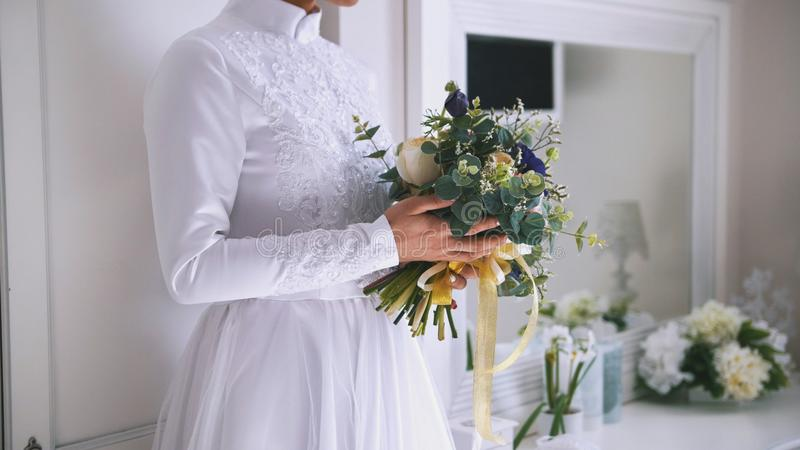 Beautiful bouquet of flowers in hands of young bride dressed in white wedding dress royalty free stock photo