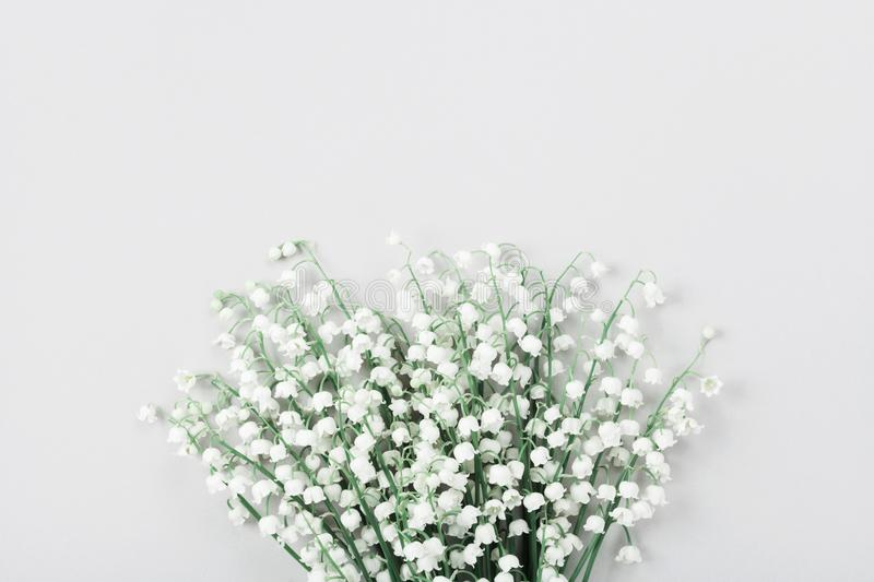 Beautiful bouquet of flowers lily of the valley on pastel table from above. Minimal composition and flat lay style. Beautiful bouquet of flowers lily of the royalty free stock image