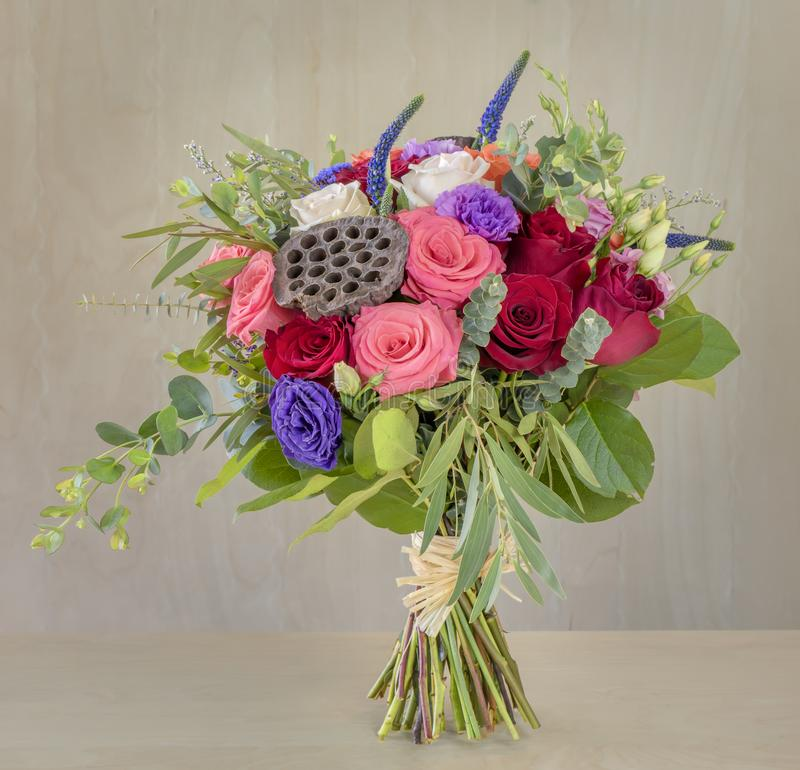 Bouquet of flowers, multi-colored roses with green leaves stock photo