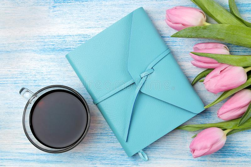 Beautiful bouquet of flowers of pink tulips and a blue notebook and a cup of coffee on a blue wooden background. top view. Spring. Holidays stock photo