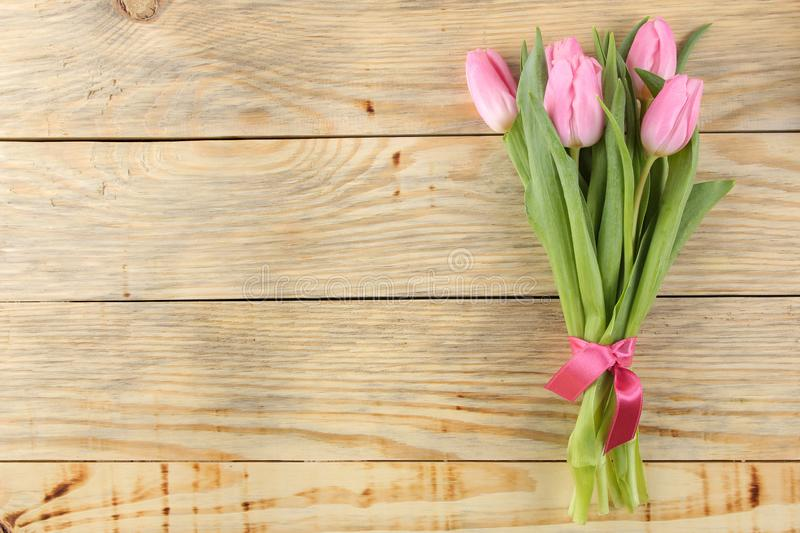 Beautiful bouquet of flowers of pink tulips on a natural wooden background. Place for text. top view. Spring. holidays stock photography
