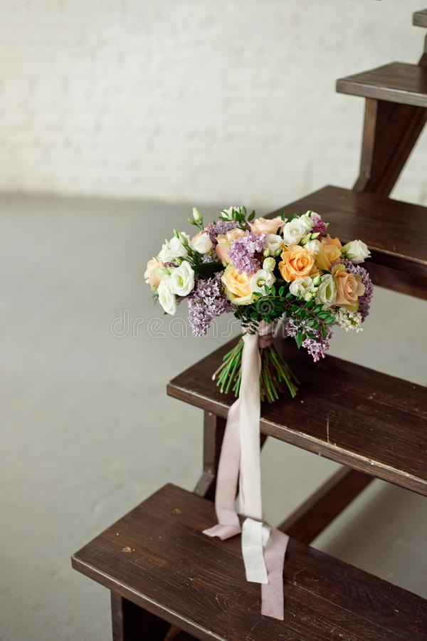 Beautiful bouquet of flowers of roses and lilac stands on a wooden ladder against a white brick wall. royalty free stock photos