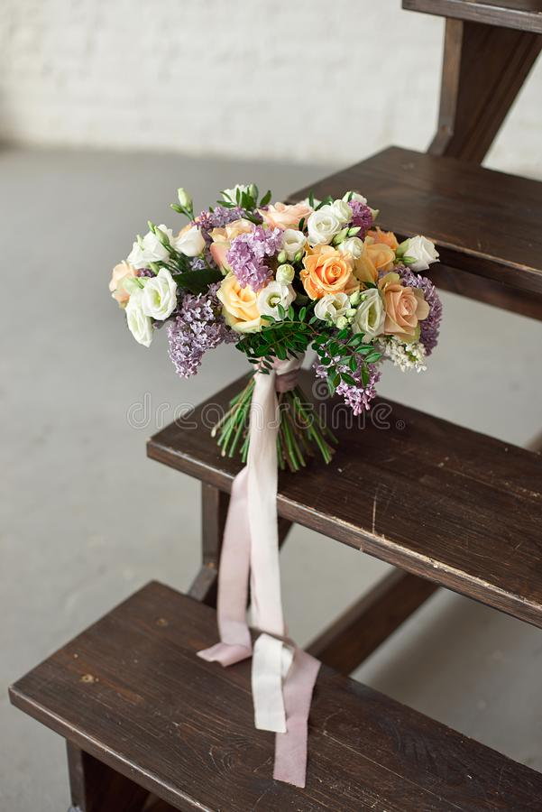 Beautiful bouquet of flowers of roses and lilac stands on a wooden ladder against a white brick wall. stock photography