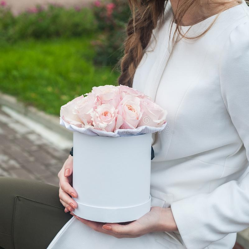 A bouquet of flowers in a hat box in the girl`s hands stock photo