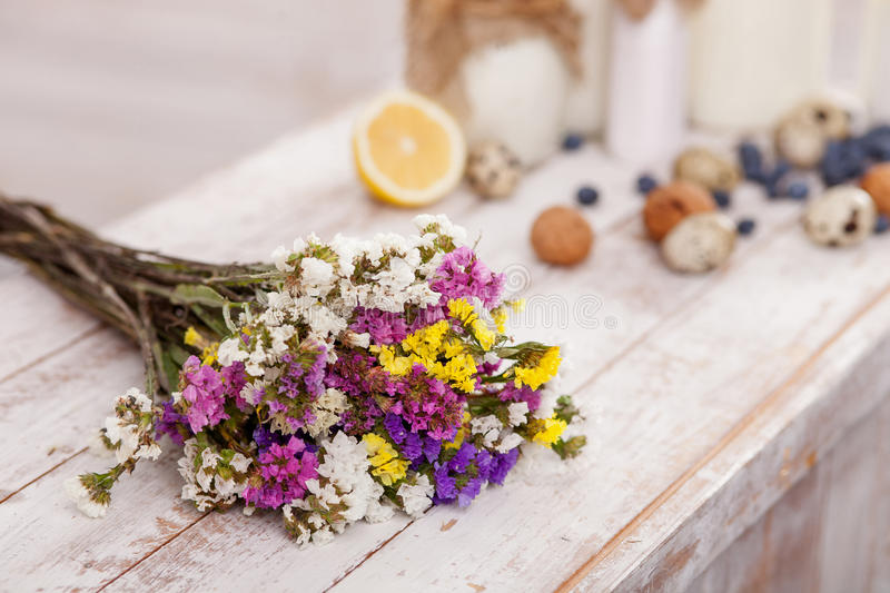 This beautiful bouquet and food is for you. Close up of pretty flowers with milk products, eggs, nuts, berry and lemon on the table royalty free stock image