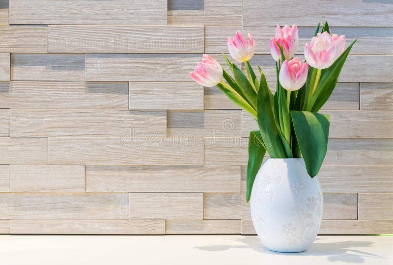 Beautiful bouquet of fresh tulips flowers against brick wall background stock image