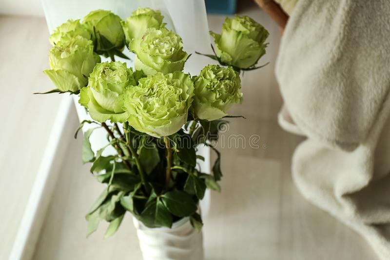 Beautiful bouquet of green roses in vase on floor in room royalty free stock images