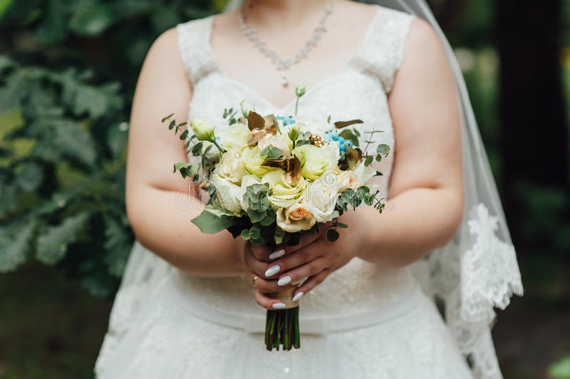 Beautiful bouquet in hands of the very fat bride stock photo