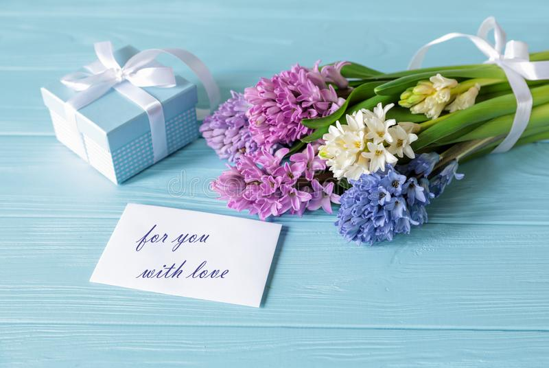 Beautiful bouquet of hyacinth flowers in pink, blue, white, violet colors and blue gift box, card with text For you with love on stock images