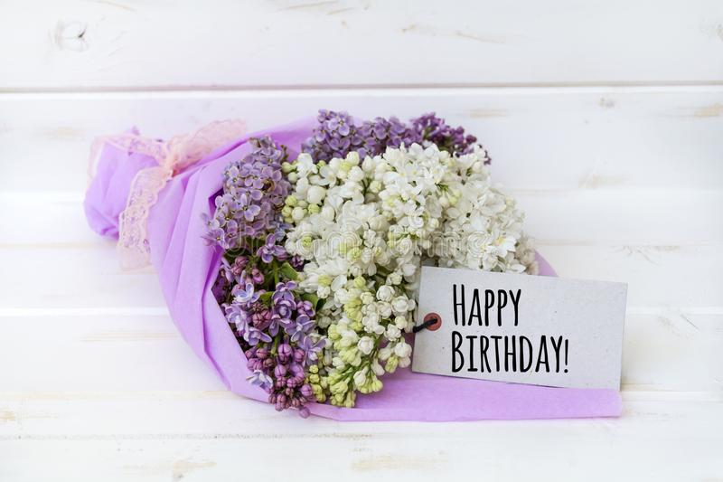 Beautiful bouquet of lilac with happy birthday card. Bouquet of purple and white lilac on a white wooden background with happy birthday message card stock images