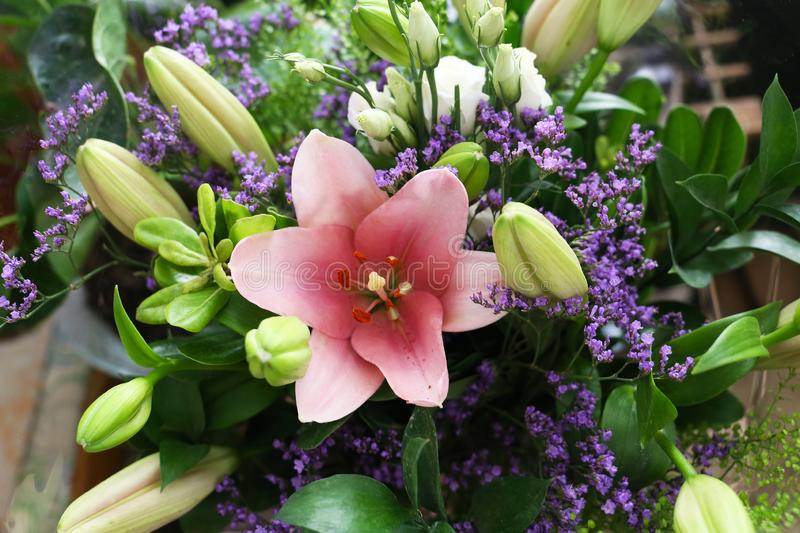 A beautiful bouquet of lilies with a big pink bud in the middle royalty free stock photography