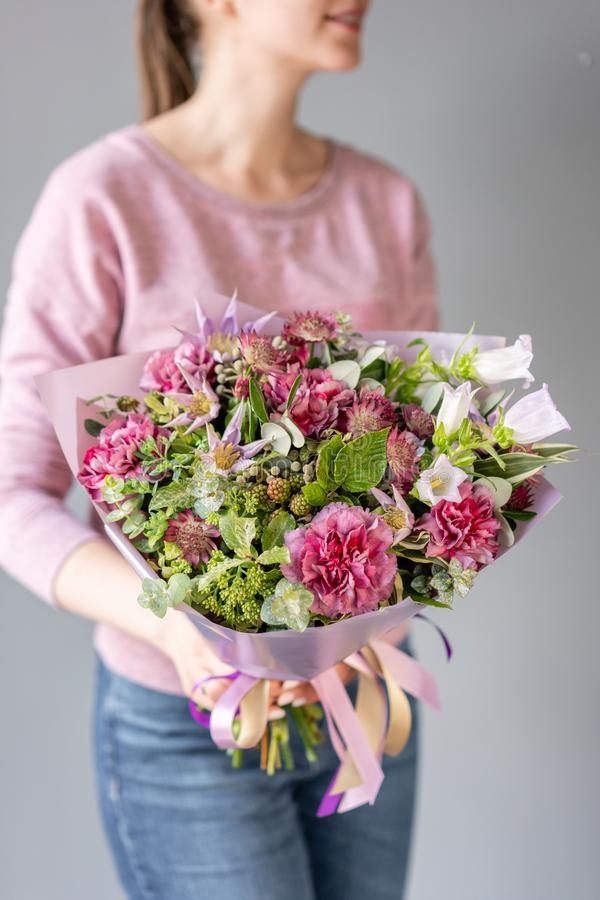 Beautiful bouquet of mixed flowers in woman hand. Floral shop concept . Handsome fresh bouquet. Flowers delivery. green royalty free stock photography