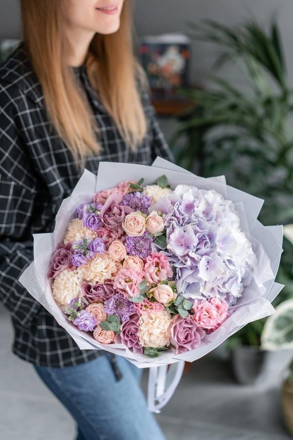 Beautiful bouquet of mixed flowers in woman hand. Floral shop concept . Handsome fresh bouquet. Flowers delivery. Red royalty free stock images