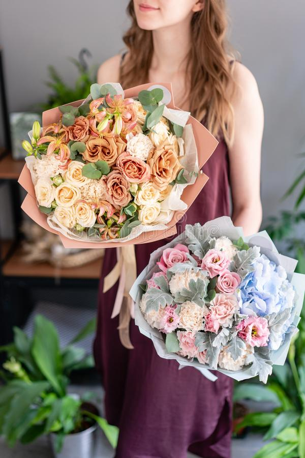 Two beautiful bouquets of mixed flowers in woman hand. Floral shop concept . Handsome fresh bouquet. Flowers delivery. royalty free stock photo