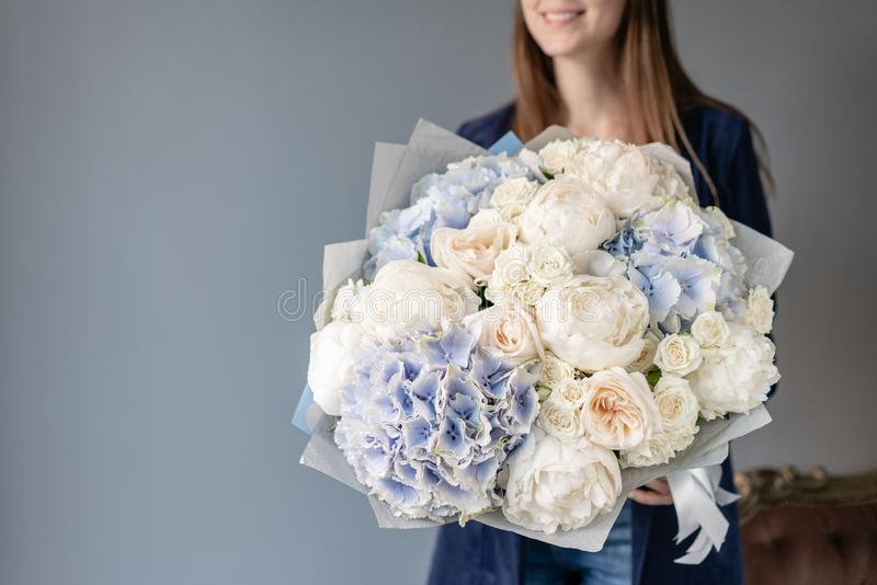 White peonies and blue hydrangea. Beautiful bouquet of mixed flowers in woman hand. Floral shop concept . Handsome fresh royalty free stock photo