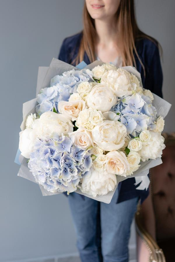 White peonies and blue hydrangea. Beautiful bouquet of mixed flowers in woman hand. Floral shop concept . Handsome fresh stock images