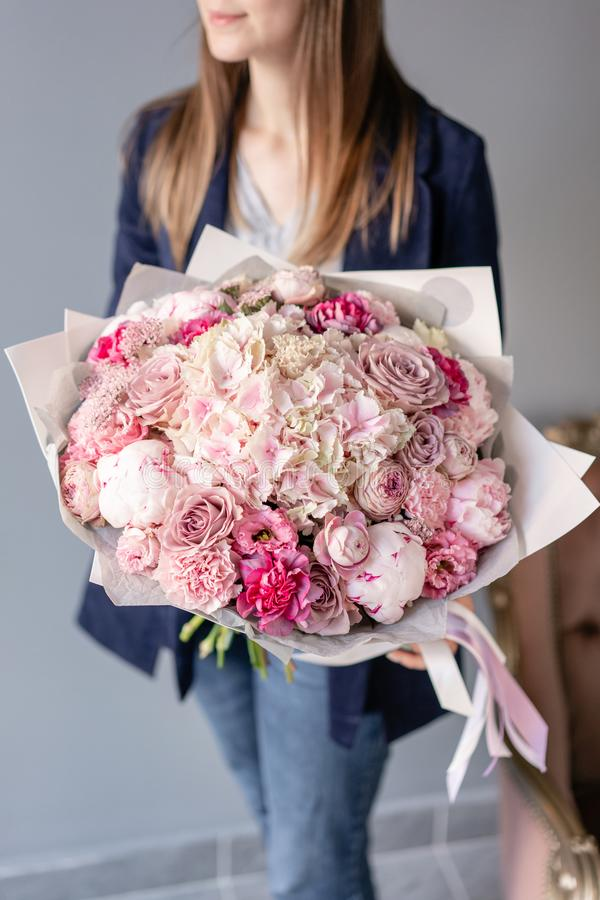 Pink peonies and hydrangea. Beautiful bouquet of mixed flowers in woman hand. Floral shop concept . Handsome fresh stock images