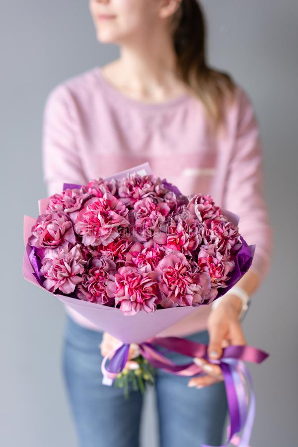 Pink and purple carnation flowers . Beautiful bouquet of mixed flowers in woman hand. Floral shop concept . Handsome stock photography