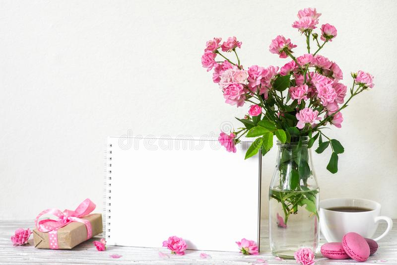 Beautiful bouquet of pink roses flowers, coffee cup, macaroons, gift box and blank white greeting card. mock up stock image