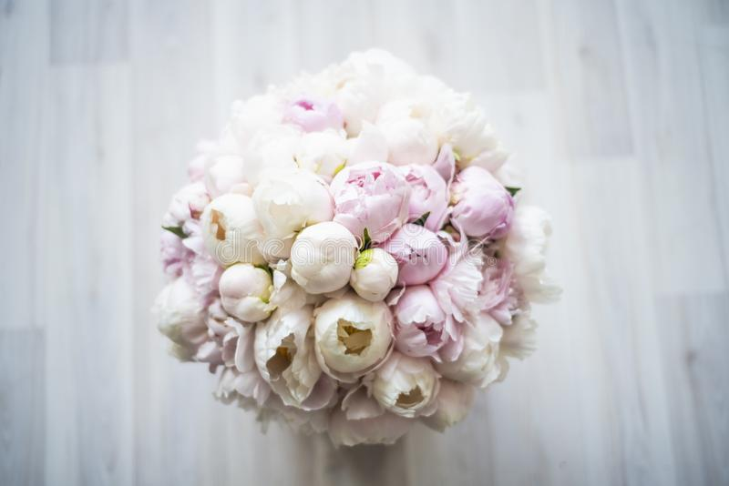 Beautiful bouquet of pink and white peonies in a box on the floor. The view from the top. royalty free stock images