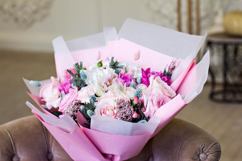 Beautiful bouquet in pink wrapping paper. Roses and other delicate beautiful flowers stock images