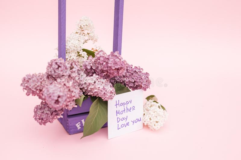 Beautiful bouquet of purple lilac and card on purple paper background royalty free stock photography