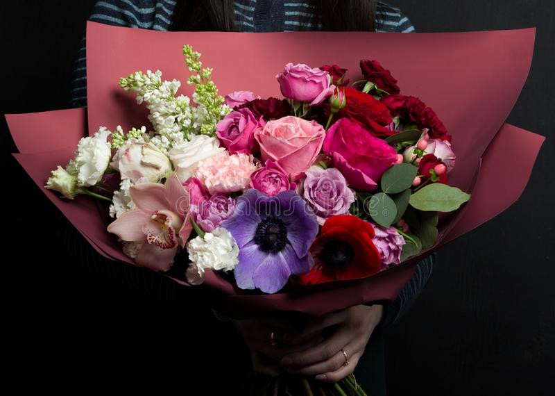 A beautiful bouquet of rare flowers with anemones, ranunculus, carnations, lilac, in the hands of a girl stock photography