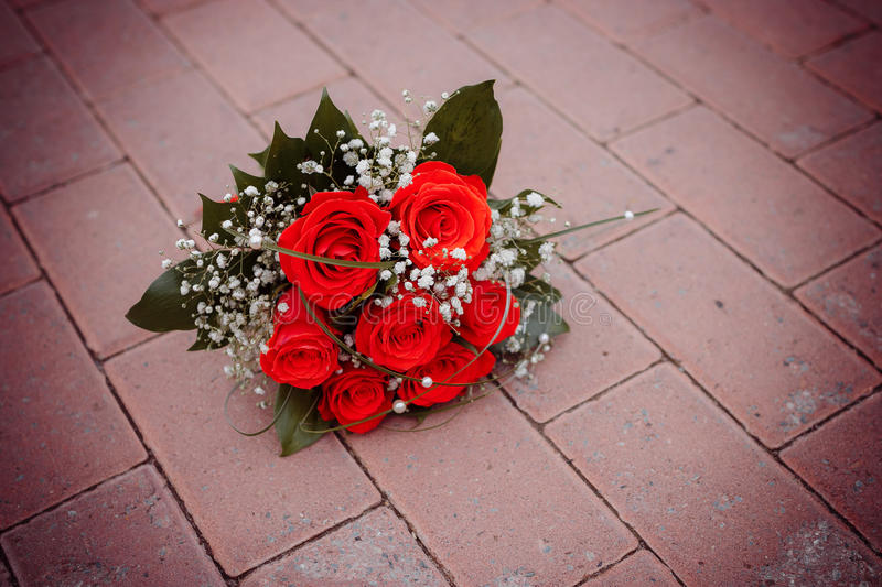 Beautiful bouquet of red rose lying on road royalty free stock photos