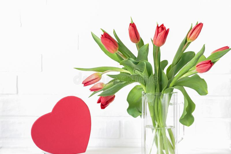 Beautiful bouquet of red tulips in a vase and red heart gift box isolated on the white background with copy space for your text, stock photos
