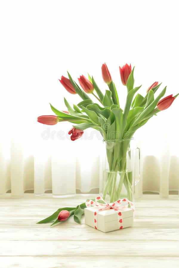 Beautiful bouquet of red tulips in a vase and small gift box on the white wooden table by the window with white curtains, stock photo